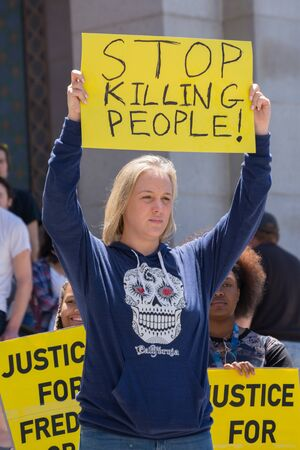 Los Angeles CA USA  May 02 2015: Woman raising a sign in march against the death of Freddie Gray a man of Baltimore who was seriously injured in police custody.