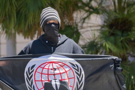 arrests: Los Angeles CA USA  May 02 2015: man holding the flag anonymous during march against the death of Freddie Gray a man of Baltimore who was seriously injured in police custody.