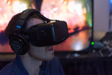 fissure: Los Angeles, CA - USA - August 29, 2015: Guy tries virtual glasses headset during VRLA Expo, virtual reality exposition, event at the Los Angeles Convention Center in Los Angeles. Éditoriale