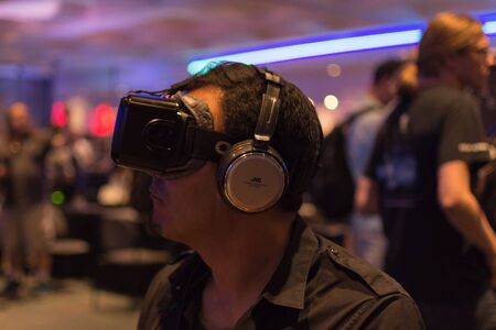 rift: Los Angeles, CA - USA - August 29, 2015: Guy tries virtual glasses headset during VRLA Expo, virtual reality exposition, event at the Los Angeles Convention Center in Los Angeles. Editorial