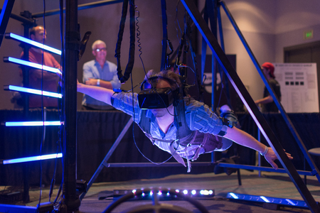 game show: Los Angeles, CA - USA - August 29, 2015: Guy tries virtual glasses headset during VRLA Expo, virtual reality exposition, event at the Los Angeles Convention Center in Los Angeles. Editorial