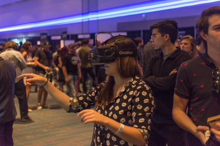 Los Angeles, CA - USA - August 29, 2015: Woman  tries virtual glasses headset during VRLA Expo, virtual reality exposition, event at the Los Angeles Convention Center in Los Angeles. Redactioneel