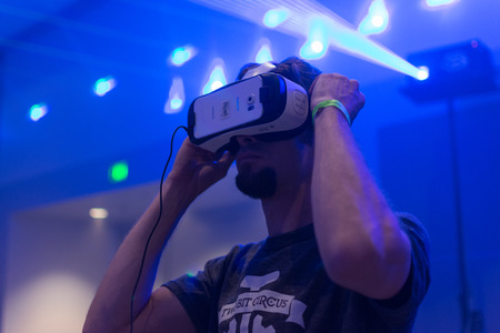 Los Angeles, CA - USA - August 29, 2015: Guy tries virtual glasses headset during VRLA Expo, virtual reality exposition, event at the Los Angeles Convention Center in Los Angeles. 新聞圖片