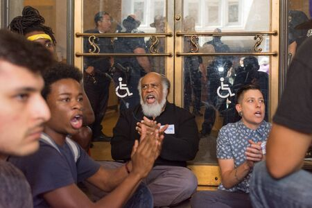 occupy movement: Los Angeles, USA - July 12, 2016 -  Black lives matter protestors  sit in front of an entrance of the City Hall following ruling on LAPD fatal shooting of African American female Redel Jones