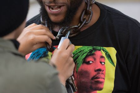 protestor: Los Angeles, USA - July 12, 2016 -  Black lives matter protestor wearing a chain with lock around his neck on City Hall following ruling on LAPD fatal shooting of African American female Redel Jones
