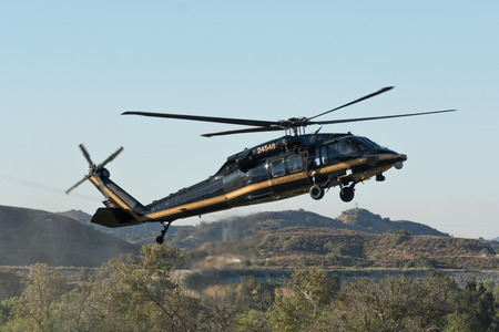 flight mode: Lakeview Terrace, USA - June 18, 2016: U.S. Customs and Border Protetion Sikorsky UH-60A Black Hawk helicopter during Los Angeles American Heroes Air Show, event designed to educate the public about rotary-wing aviation.