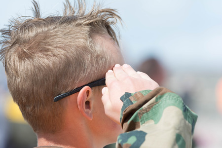 Lancaster, USA - March 25, 2017: Teen salute during National Anthem on display during Los Angeles County Air Show at the William J Fox Airfield.