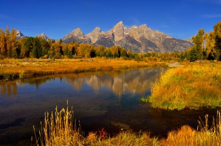 Snow-capped mountains and fall reflections Stock Photo