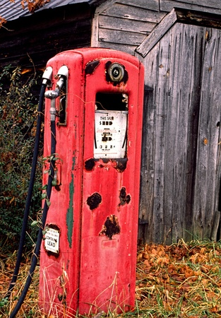 An old rustic red gas pump sits idle  photo