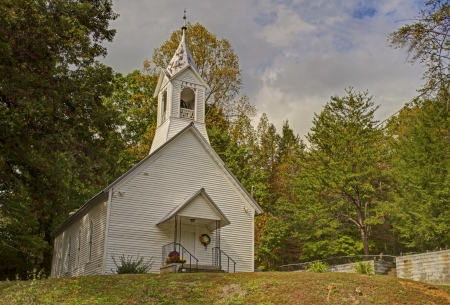 A little white church is surrounded by fall leaves