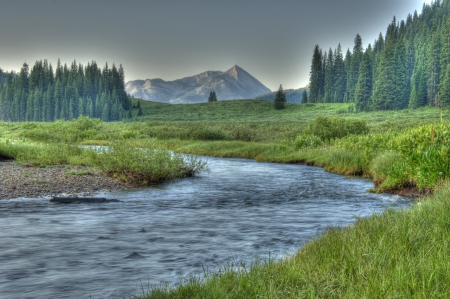Clean river leading into snow capped mountains in The Grand Tetons  photo