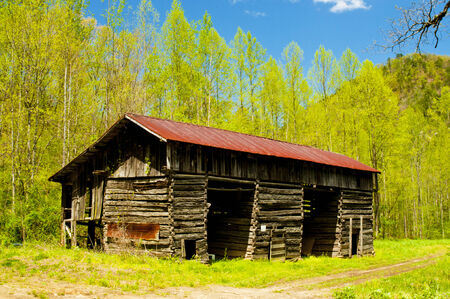 Rustic old log barn with red roof tin still standing