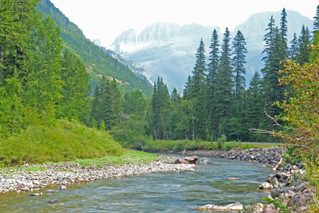 Clear blue stream and snowy mountains in Glacier National Park. photo