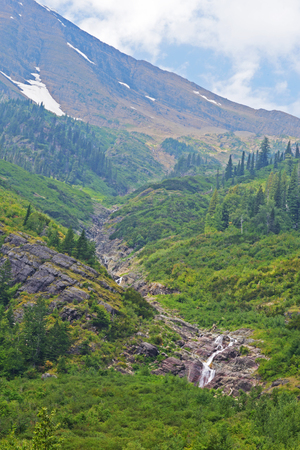 Waterfalls and snow in Glacier National Park. photo