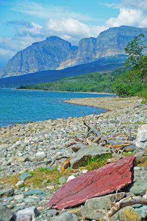 Vertical red rock on the shoreline of a clear blue lake. photo