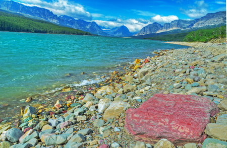 Red rocks on the shore of a clear blue lake. photo