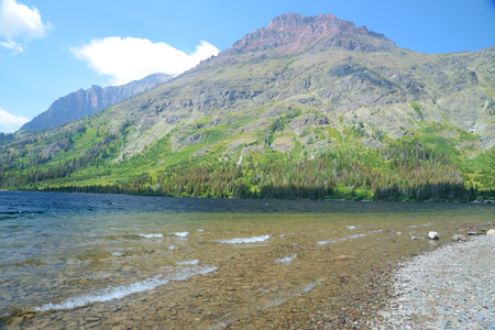 Lakeshore of rocks and clear waters in Glacier. photo