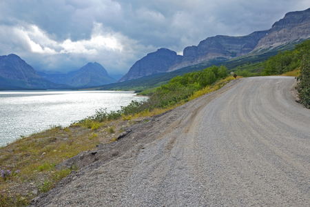 Highway beside a clear blue lake in Glacier National Park. photo