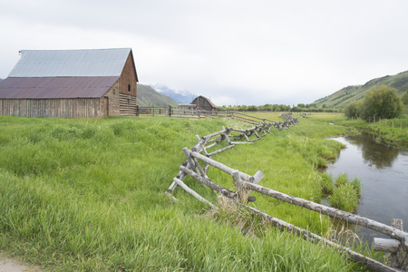 surrounds: Wooden rail fence surrounds a small creek and old barn.