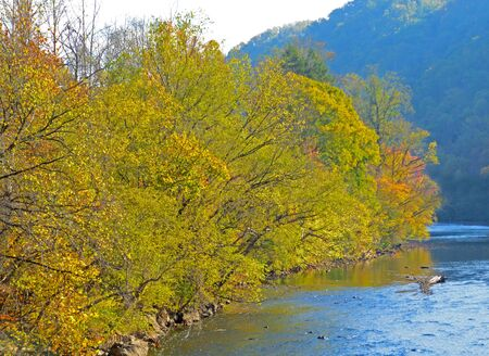 the smokies: Smokies fall colors on lazy river and blue mountains.