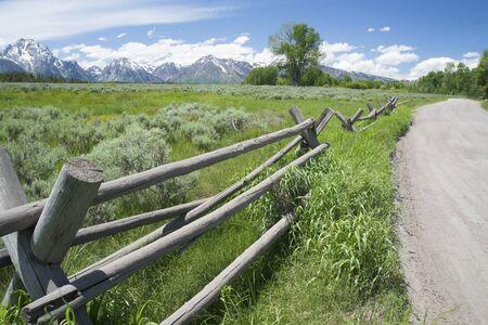 split road: Split rail fence along a gravel road in Wyoming