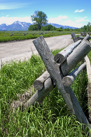 fenceline: Vertical-split rail fence along mountain road.