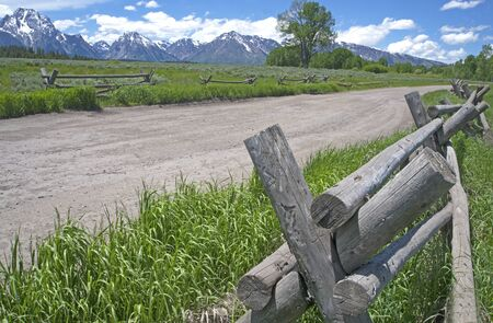 fenceline: Wooden split rail fence along country road in Wyoming. Stock Photo