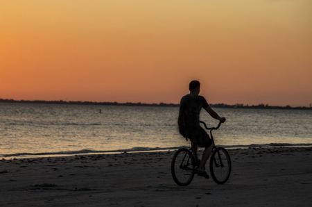 Silhouette of male riding a bicycle on the beach at sunset. Imagens