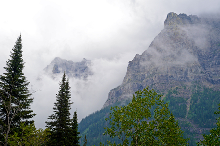 Fog lies around massive mountains in Glacier.