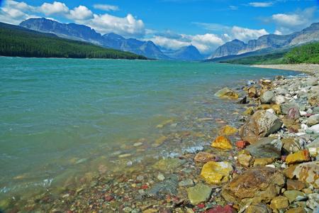 Les rochers bordent la bordure d'un lac bleu clair dans le parc national des Glaciers. Banque d'images - 79095526
