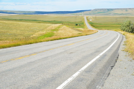 Long winding empty road is in Montana. Stock Photo