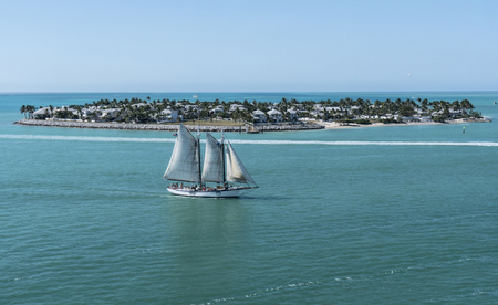 A sailboat with full sails moves past an island in the Bahamas. Editorial