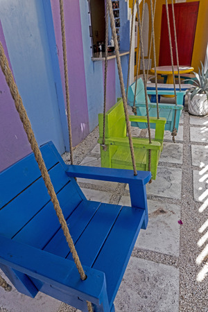 Vertical-Colorful swings hang by a rope in the Bahamas. Standard-Bild