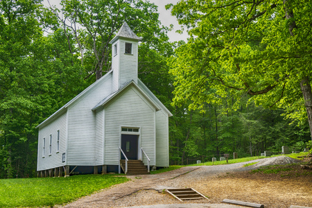 A little white country church is surrounded with greenery. Stock Photo