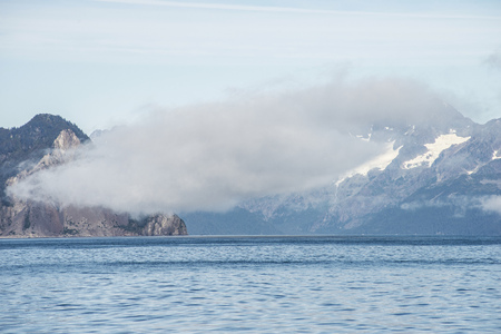 Fog lies over the mountains and waters of Resurrection Bay in Alaska.