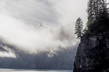 Clouds travel around cliffs in Resurrection Bay, Alaska.