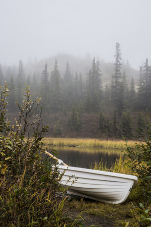 A little white boat sits beside a kettle pond in Alaska. Stock Photo