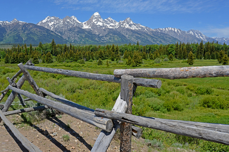 A split rail fence beneath snow capped mountains in the Grand Tetons.
