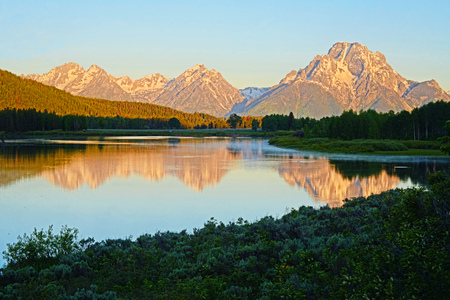 Sunrise over a clean lake in The Grand Tetons. Stock Photo