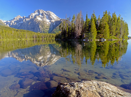 Snow capped mountains and water reflections in Yellowstone.