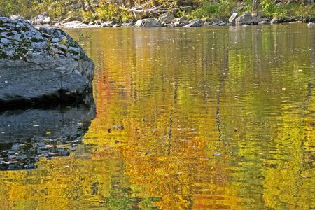 Orange and yellow water reflections along the Pigeon River.