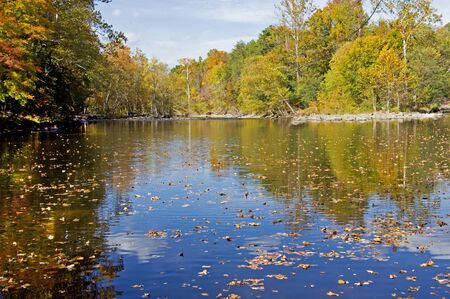 Colored water reflections along the Pigeon River in fall.
