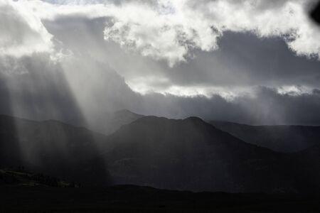 Sun streaks shade a mountain in Yellowstone.