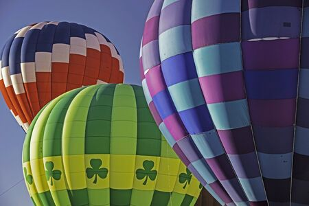 Colorful hot air balloons against a clear blue sky.