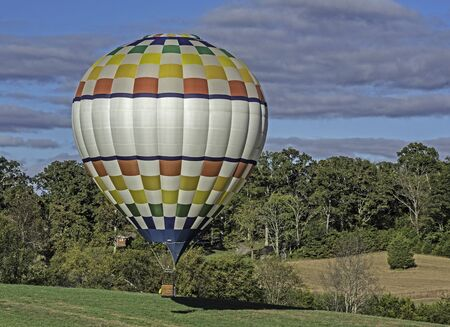 Hot air balloon floats away over the grassy field.