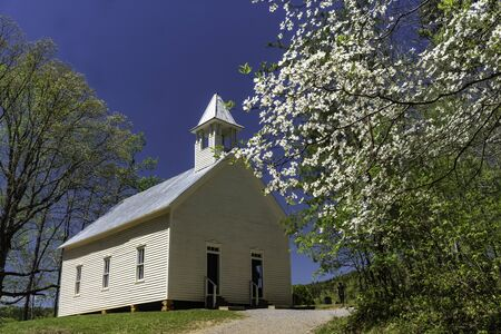 Little white country church surrounded with Dogwood blooms. Stock Photo