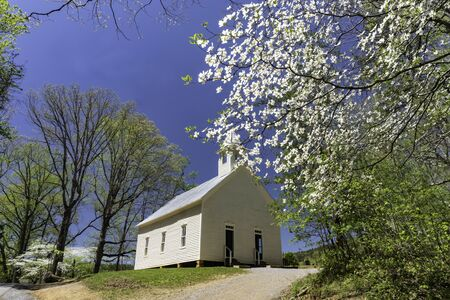 Little white country church under a blue sky. Stock Photo