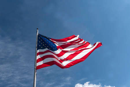 United States flag flies in the wind beneath clear blue skies.