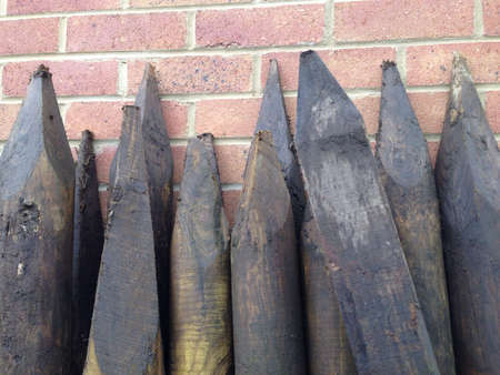 fence: The sharpened pointed ends of wooden fence posts leaning against a brick wall Stock Photo