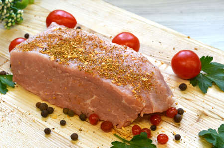 Raw pork meat on cutting board and vegetables and greens.